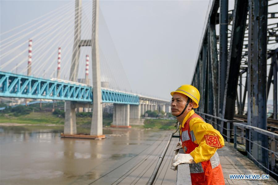 Tang Jinhua looks at the new Baishatuo Yangtze River railway bridge in Jiangjin of southwest China\'s Chongqing Municipality, April 23, 2019. The previous Baishatuo Yangtze River railway bridge, completed in 1959, will stop service after April 24. All trains will run on the new double decker steel truss cable stay railway bridge after that day. The new bridge has 4 tracks on the upper deck for passenger trains with a designed speed of 200 kilometers per hour and 2 tracks on the lower deck for cargo trains with the designed speed of 120 kilometers per hour. (Xinhua/Liu Chan)