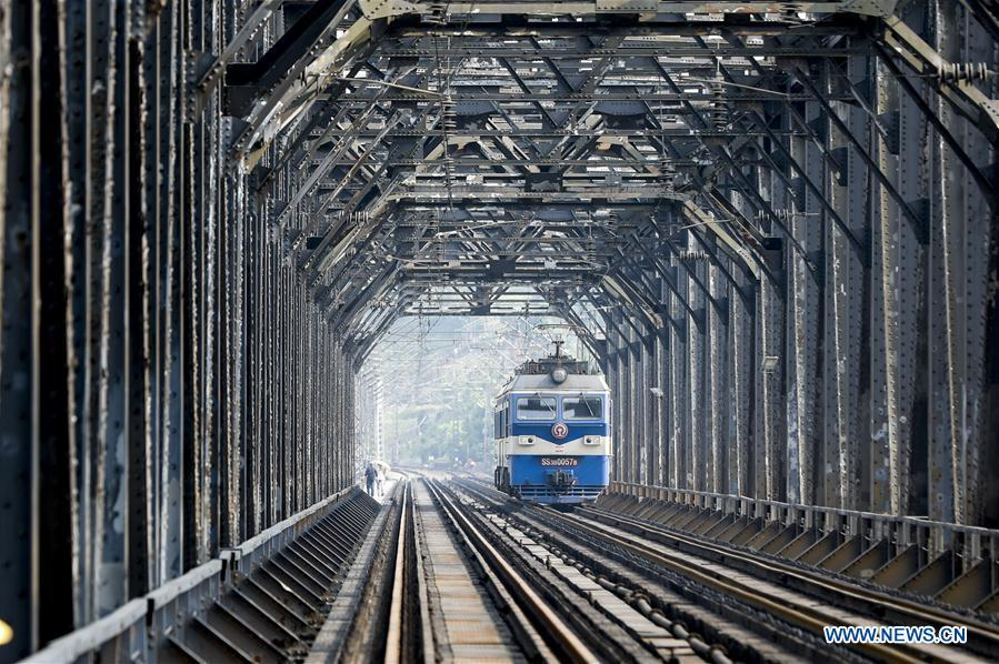 An electrical locomotive runs on the previous Baishatuo Yangtze River railway bridge in Jiangjin of southwest China\'s Chongqing Municipality, April 23, 2019. The previous Baishatuo Yangtze River railway bridge, completed in 1959, will stop service after April 24. All trains will run on the new double decker steel truss cable stay railway bridge after that day. The new bridge has 4 tracks on the upper deck for passenger trains with a designed speed of 200 kilometers per hour and 2 tracks on the lower deck for cargo trains with the designed speed of 120 kilometers per hour. (Xinhua/Liu Chan)