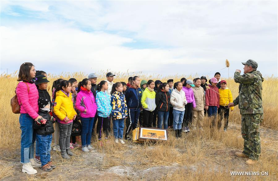 Shuanglong, a man of Mongolian ethnic group, explains knowledge on wildlife protection to primary students at the reeds along the Hulun Lake in the Hulun Buir City, north China\'s Inner Mongolia Autonomous Region, April 13, 2019. Shuanglong, a volunteer born in the 1980s, has been dedicated to protecting wildlife inhabiting along the Hulun Lake over the past ten years. Over 40 endangered animals have been saved through his efforts. Shuanglong has organized various activities including photo exhibitions and lectures, as a way to raise awareness of wildlife protection among the public. Affected by Shuanglong, some volunteers also joined him to protect wildlife along the Hulun Lake. (Xinhua/Peng Yuan)