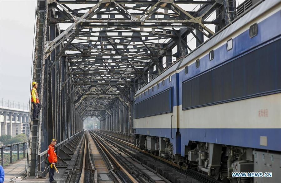 Workers wait for an electrical locomotive to pass on the previous Baishatuo Yangtze River railway bridge in Jiangjin of southwest China\'s Chongqing Municipality, April 23, 2019. The previous Baishatuo Yangtze River railway bridge, completed in 1959, will stop service after April 24. All trains will run on the new double decker steel truss cable stay railway bridge after that day. The new bridge has 4 tracks on the upper deck for passenger trains with a designed speed of 200 kilometers per hour and 2 tracks on the lower deck for cargo trains with the designed speed of 120 kilometers per hour. (Xinhua/Liu Chan)