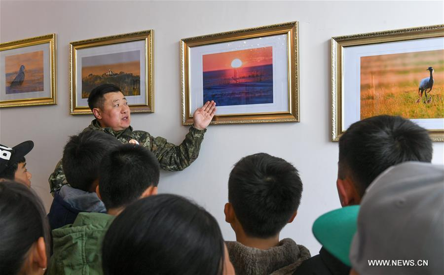 Shuanglong, a man of Mongolian ethnic group, leads primary students to visit his photo exhibition in New Barag Right Banner of the Hulun Buir City, north China\'s Inner Mongolia Autonomous Region, April 13, 2019. Shuanglong, a volunteer born in the 1980s, has been dedicated to protecting wildlife inhabiting along the Hulun Lake over the past ten years. Over 40 endangered animals have been saved through his efforts. Shuanglong has organized various activities including photo exhibitions and lectures, as a way to raise awareness of wildlife protection among the public. Affected by Shuanglong, some volunteers also joined him to protect wildlife along the Hulun Lake. (Xinhua/Peng Yuan)