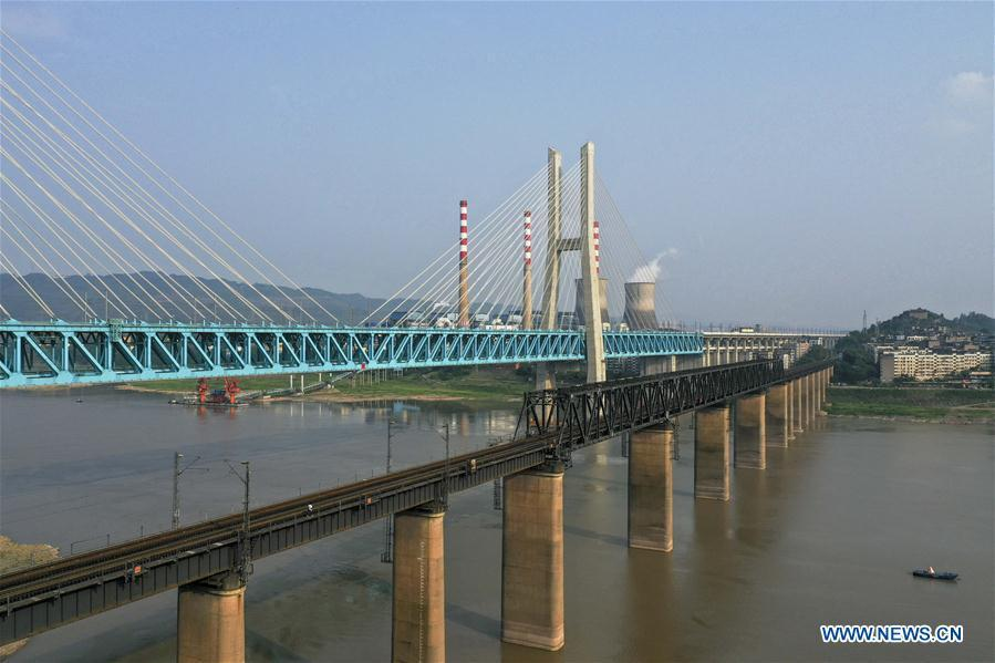 Aerial photo taken on April 23, 2019 shows the previous (R) and the new Baishatuo Yangtze River railway bridge in Jiangjin of southwest China\'s Chongqing Municipality. The previous Baishatuo Yangtze River railway bridge, completed in 1959, will stop service after April 24. All trains will run on the new double decker steel truss cable stay railway bridge after that day. The new bridge has 4 tracks on the upper deck for passenger trains with a designed speed of 200 kilometers per hour and 2 tracks on the lower deck for cargo trains with the designed speed of 120 kilometers per hour. (Xinhua/Liu Chan)