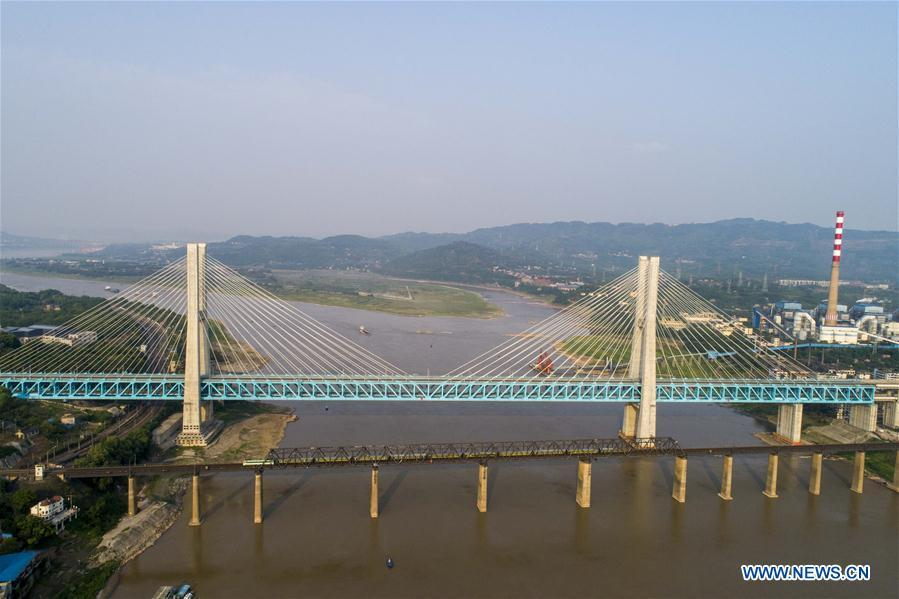 Aerial photo shows the last train running on the previous Baishatuo Yangtze River railway bridge (Front) in Jiangjin of southwest China\'s Chongqing Municipality, on April 23, 2019. The previous Baishatuo Yangtze River railway bridge, completed in 1959, will stop service after April 24. All trains will run on the new double decker steel truss cable stay railway bridge after that day. The new bridge has 4 tracks on the upper deck for passenger trains with a designed speed of 200 kilometers per hour and 2 tracks on the lower deck for cargo trains with the designed speed of 120 kilometers per hour. (Xinhua/Liu Chan)