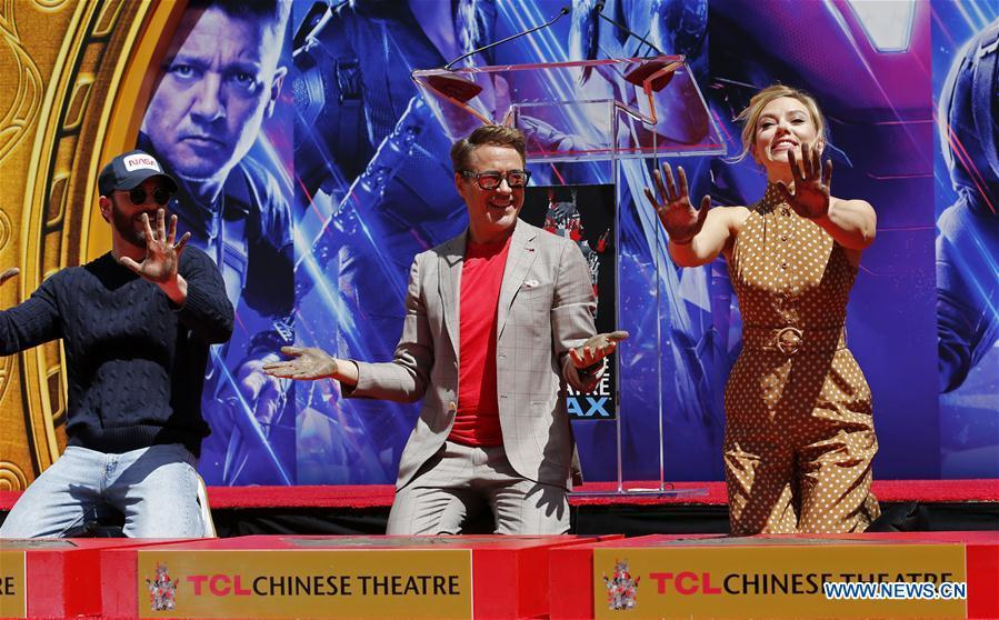 Actor Robert Downey Jr. (C), Chris Evans (L) and actress Scarlett Johansson show their hands after putting their handprints in cement during print ceremony in the forecourt of the TCL Chinese Theater in Los Angeles, the United States, April 23, 2019. The cast of Marvel Studios \
