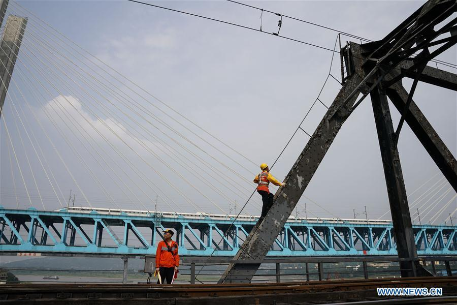 Workers of China Railway Chengdu Group Co., Ltd. conduct final check on the previous Baishatuo Yangtze River railway bridge in Jiangjin of southwest China\'s Chongqing Municipality, April 23, 2019. The previous Baishatuo Yangtze River railway bridge, completed in 1959, will stop service after April 24. All trains will run on the new double decker steel truss cable stay railway bridge after that day. The new bridge has 4 tracks on the upper deck for passenger trains with a designed speed of 200 kilometers per hour and 2 tracks on the lower deck for cargo trains with the designed speed of 120 kilometers per hour. (Xinhua/Liu Chan)