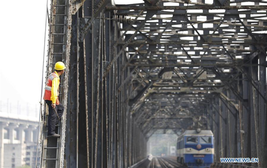 A worker waits for an electrical locomotive to pass on the previous Baishatuo Yangtze River railway bridge in Jiangjin of southwest China\'s Chongqing Municipality, April 23, 2019. The previous Baishatuo Yangtze River railway bridge, completed in 1959, will stop service after April 24. All trains will run on the new double decker steel truss cable stay railway bridge after that day. The new bridge has 4 tracks on the upper deck for passenger trains with a designed speed of 200 kilometers per hour and 2 tracks on the lower deck for cargo trains with the designed speed of 120 kilometers per hour. (Xinhua/Liu Chan)