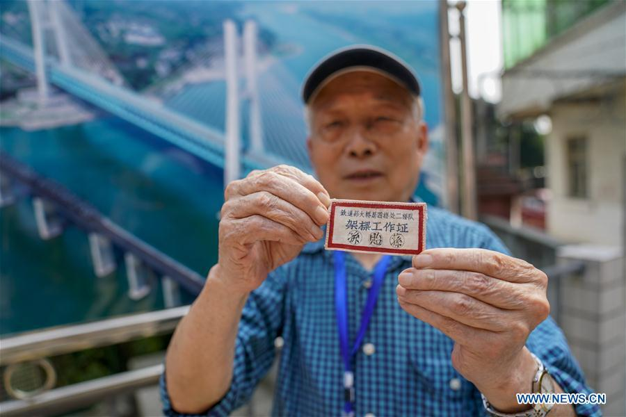 Sun Yisun, a former builder of the previous Baishatuo Yangtze River railway bridge, shows his old employee\'s card in Jiangjin of southwest China\'s Chongqing Municipality, April 23, 2019. The previous Baishatuo Yangtze River railway bridge, completed in 1959, will stop service after April 24. All trains will run on the new double decker steel truss cable stay railway bridge after that day. The new bridge has 4 tracks on the upper deck for passenger trains with a designed speed of 200 kilometers per hour and 2 tracks on the lower deck for cargo trains with the designed speed of 120 kilometers per hour. (Xinhua/Liu Chan)