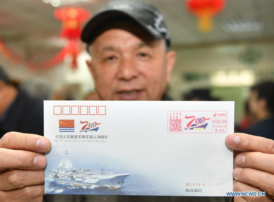 67-year-old Dai Chunguang displays a commemorative envelope at a shop in Qingdao, east China\'s Shandong Province, April 23, 2019. A set of philatelic items were issued on Tuesday to mark the 70th founding anniversary of the Chinese People\'s Liberation Army (PLA) Navy. (Xinhua/Zhu Zheng)
