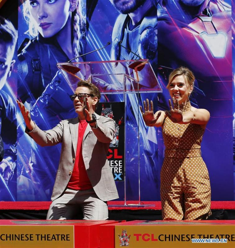 Actor Robert Downey Jr. (L) and actress Scarlett Johansson show their hands after putting their handprints in cement during print ceremony in the forecourt of the TCL Chinese Theater in Los Angeles, the United States, April 23, 2019. The cast of Marvel Studios \