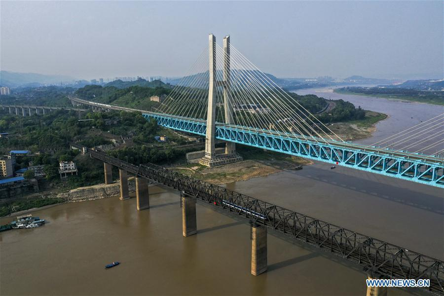 Aerial photo taken on April 23, 2019 shows the previous (L) and the new Baishatuo Yangtze River railway bridge in Jiangjin of southwest China\'s Chongqing Municipality. The previous Baishatuo Yangtze River railway bridge, completed in 1959, will stop service after April 24. All trains will run on the new double decker steel truss cable stay railway bridge after that day. The new bridge has 4 tracks on the upper deck for passenger trains with a designed speed of 200 kilometers per hour and 2 tracks on the lower deck for cargo trains with the designed speed of 120 kilometers per hour. (Xinhua/Liu Chan)