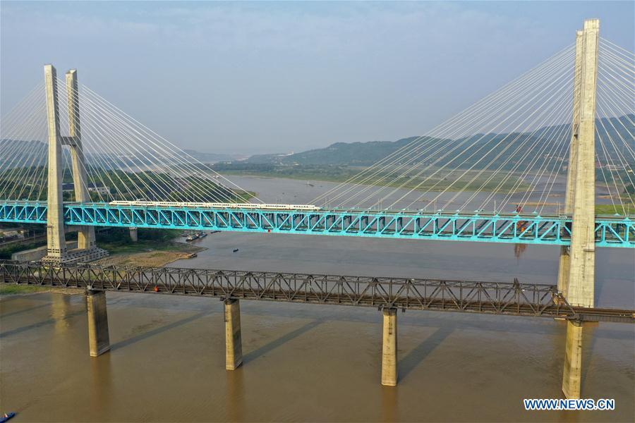 Aerial photo taken on April 23, 2019 shows a bullet train running on the new Baishatuo Yangtze River railway bridge (Back) in Jiangjin of southwest China\'s Chongqing Municipality. The previous Baishatuo Yangtze River railway bridge, completed in 1959, will stop service after April 24. All trains will run on the new double decker steel truss cable stay railway bridge after that day. The new bridge has 4 tracks on the upper deck for passenger trains with a designed speed of 200 kilometers per hour and 2 tracks on the lower deck for cargo trains with the designed speed of 120 kilometers per hour. (Xinhua/Liu Chan)