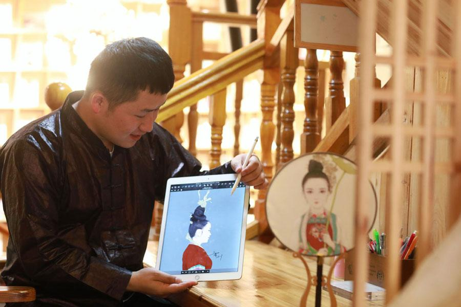 Lan Caisheng shows a drawing of a woman dressed in Dong ethnic clothes at the gallery in Zhaoxing Dong village, Liping county, Southwest China\'s Guizhou Province, April 16, 2019. (Photo/Xinhua)