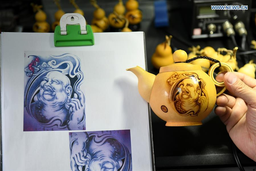 Craftsman Liu Chunpu compares the cucurbits pyrography work with a design drawing at a studio in Yuhua District of Shijiazhuang, north China\'s Hebei Province, April 23, 2019. Liu Chunpu, a staff member of Hebei Normal University, has devoted himself in cucurbit pyrography for more than 40 years. (Xinhua/Xu Jianyuan)