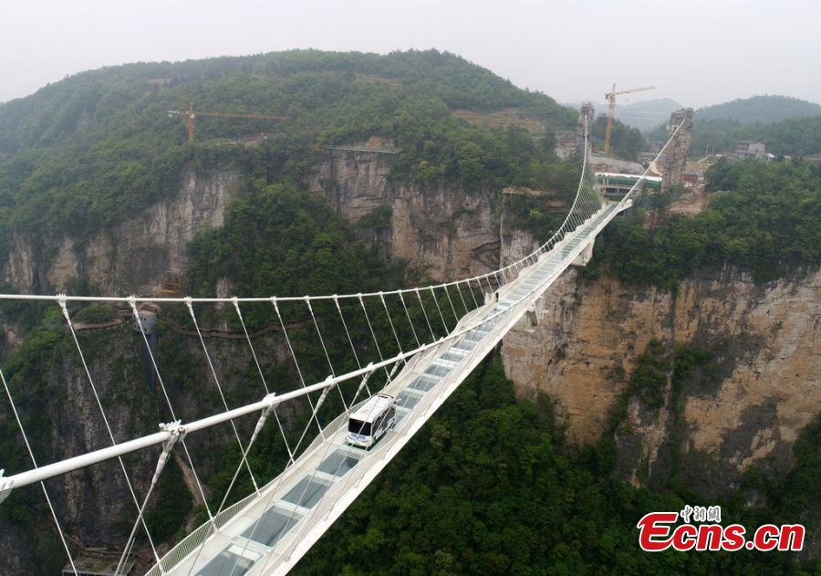 An automated bus drives on the glass bridge of the Grand Canyon scenic area in Zhangjiajie, Hunan Province, on April 24, 2019. The scenic area will offer the self-driving bus service, which can carry 25 people and reach a speed of up to 40 kilometers per hour.  (Photo/IC)