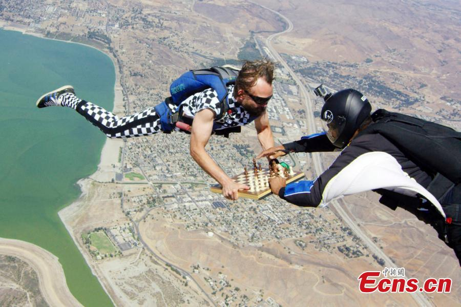 Timur Faridovich Gareyev is pictured skydiving while holding a chess board. 31-year-old Timur is a chess player from Tashkent, Uzbekistan. He is also an experienced skydiver with 150 jumps under his belt. He jumped from the aircraft wearing a chequered jumpsuit with the chess pieces fixed onto the board on his way to contest a San Diego Chess Open in California. (Photo/IC)