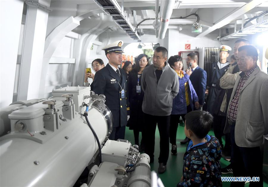 A crew member introduces torpedo installations to visitors on the guided-missile destroyer Guiyang of the Chinese People\'s Liberation Army (PLA) Navy during a warship open day event in Qingdao, east China\'s Shandong Province, April 24, 2019. A warship open day event was held on Wednesday in Qingdao, as part the multinational naval events marking the 70th founding anniversary of PLA Navy. (Xinhua/Yu Lan)