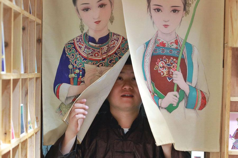 Lan Caisheng steps through curtains featuring his drawings in Zhaoxing Dong village, Liping county, Southwest China\'s Guizhou Province, April 16, 2019. (Photo/Xinhua)