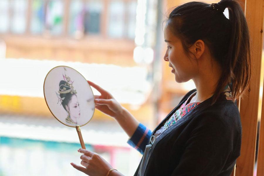 A Dong woman looks at a drawing by Lan Caisheng in Zhaoxing Dong village, Liping county, Southwest China\'s Guizhou Province, April 16, 2019. (Photo/Xinhua)