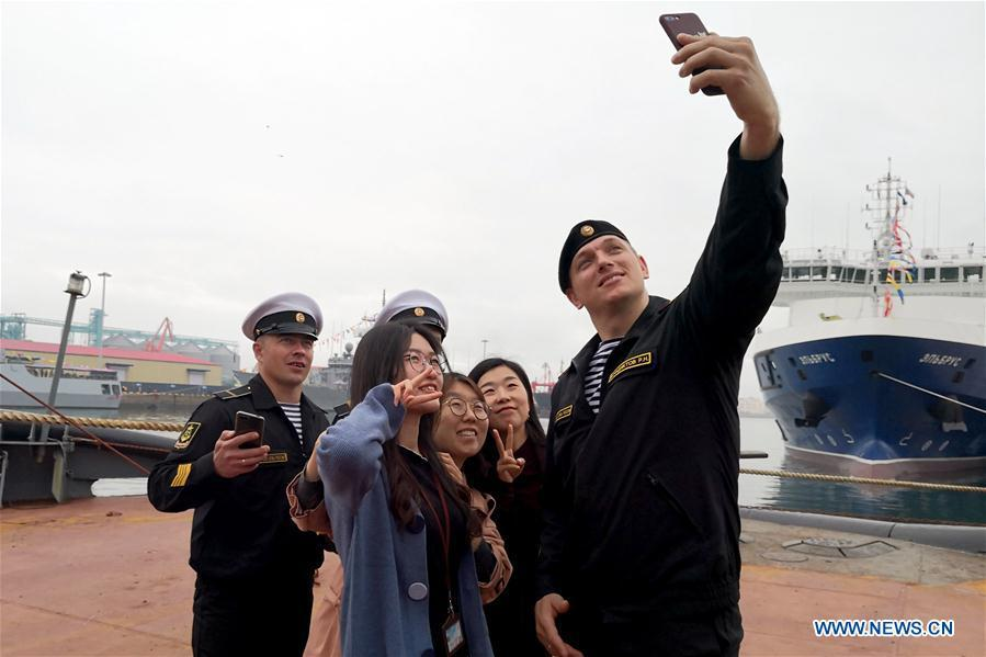 Crew members and visitors take a selfie on Russian Navy tug ship Nikolai Chiker during a warship open day event in Qingdao, east China\'s Shandong Province, April 24, 2019. A warship open day event was held on Wednesday in Qingdao, as part the multinational naval events marking the 70th founding anniversary of PLA Navy. (Xinhua/Yu Lan)