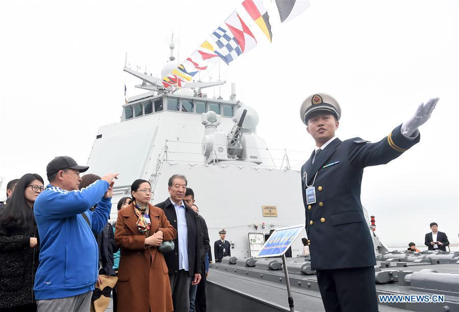 An interpreter introduces the guided-missile destroyer Guiyang of the Chinese People\'s Liberation Army (PLA) Navy to visitors during a warship open day event in Qingdao, east China\'s Shandong Province, April 24, 2019. A warship open day event was held on Wednesday in Qingdao, as part the multinational naval events marking the 70th founding anniversary of PLA Navy. (Xinhua/Luo Xiaoguang)