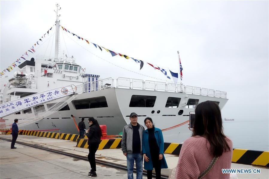 Visitors pose for a photo in front of hospital ship Peace Ark of the Chinese People\'s Liberation Army (PLA) Navy during a warship open day event in Qingdao, east China\'s Shandong Province, April 24, 2019. A warship open day event was held on Wednesday in Qingdao, as part the multinational naval events marking the 70th founding anniversary of PLA Navy. (Xinhua/Ma Jing)