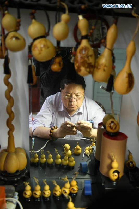 Craftsman Liu Chunpu creates cucurbit pyrography at a studio in Yuhua District of Shijiazhuang, north China\'s Hebei Province, April 23, 2019. Liu Chunpu, a staff member of Hebei Normal University, has devoted himself in cucurbit pyrography for more than 40 years. (Xinhua/Xu Jianyuan)