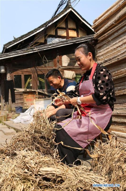 Wang Xingwu (L), a paper maker, tidies papermaking materials with his wife in Shiqiao Village of Danzhai County, southwest China\'s Guizhou Province, April 24, 2019. Wang Xingwu, 53, a national intangible cultural heritage inheritor in papermaking, learned the papermaking technique from his family as a child. Besides exerting the old papermaking technique to its full potential, Wang keeps raising product quality and improving the making procedure. With the involvement of plants in the papermaking process, he has created more than 160 kinds of patterned papers and paper crafts. He also develops a kind of handmade white paper more suitable for writing calligraphy and painting. (Xinhua/Huang Xiaohai)