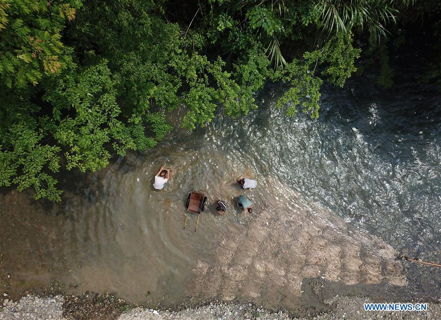 Aerial photo shows craftsmen washing raw materials in a river in Shiqiao Village of Danzhai County, southwest China\'s Guizhou Province, April 24, 2019. Wang Xingwu, 53, a national intangible cultural heritage inheritor in papermaking, learned the papermaking technique from his family as a child. Besides exerting the old papermaking technique to its full potential, Wang keeps raising product quality and improving the making procedure. With the involvement of plants in the papermaking process, he has created more than 160 kinds of patterned papers and paper crafts. He also develops a kind of handmade white paper more suitable for writing calligraphy and painting. (Xinhua/Huang Xiaohai)