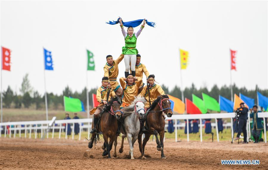 People make a human pyramid on horses at the Genghis Khan Chagan Suluk Nadam Fair in Ejin Horo Banner of Ordos City, north China\'s Inner Mongolia Autonomous Region, April 24, 2019. The two-day fair kicked off on Wednesday, including a variety of traditional activities. (Xinhua/Peng Yuan)