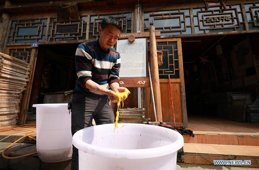 Wang Xingwu, a papermaker, checks colored paper pulp made from plants at a workshop in Shiqiao Village of Danzhai County, southwest China\'s Guizhou Province, April 24, 2019. Wang Xingwu, 53, a national intangible cultural heritage inheritor in papermaking, learned the papermaking technique from his family as a child. Besides exerting the old papermaking technique to its full potential, Wang keeps raising product quality and improving the making procedure. With the involvement of plants in the papermaking process, he has created more than 160 kinds of patterned papers and paper crafts. He also develops a kind of handmade white paper more suitable for writing calligraphy and painting. (Xinhua/Huang Xiaohai)