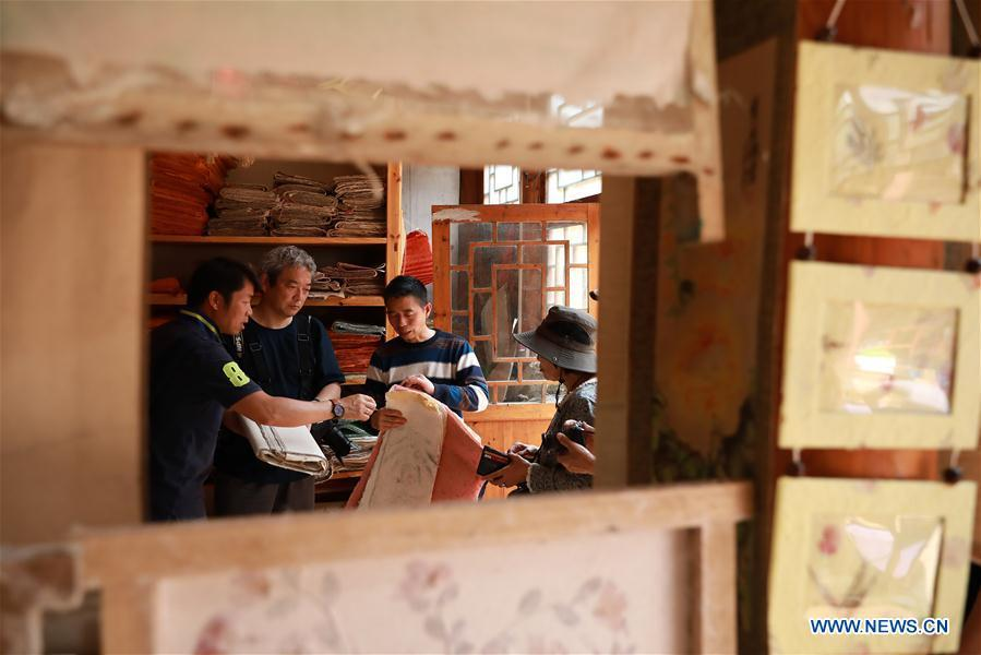 Wang Xingwu (2nd L), a paper maker, introduces his paper product to Japanese tourists at a workshop in Shiqiao Village of Danzhai County, southwest China\'s Guizhou Province, April 24, 2019. Wang Xingwu, 53, a national intangible cultural heritage inheritor in papermaking, learned the papermaking technique from his family as a child. Besides exerting the old papermaking technique to its full potential, Wang keeps raising product quality and improving the making procedure. With the involvement of plants in the papermaking process, he has created more than 160 kinds of patterned papers and paper crafts. He also develops a kind of handmade white paper more suitable for writing calligraphy and painting. (Xinhua/Huang Xiaohai)