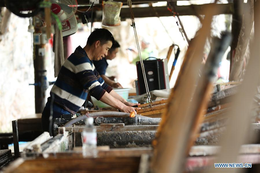 Wang Xingwu makes paper at a workshop in Shiqiao Village of Danzhai County, southwest China\'s Guizhou Province, April 24, 2019. Wang Xingwu, 53, a national intangible cultural heritage inheritor in papermaking, learned the papermaking technique from his family as a child. Besides exerting the old papermaking technique to its full potential, Wang keeps raising product quality and improving the making procedure. With the involvement of plants in the papermaking process, he has created more than 160 kinds of patterned papers and paper crafts. He also develops a kind of handmade white paper more suitable for writing calligraphy and painting. (Xinhua/Huang Xiaohai)