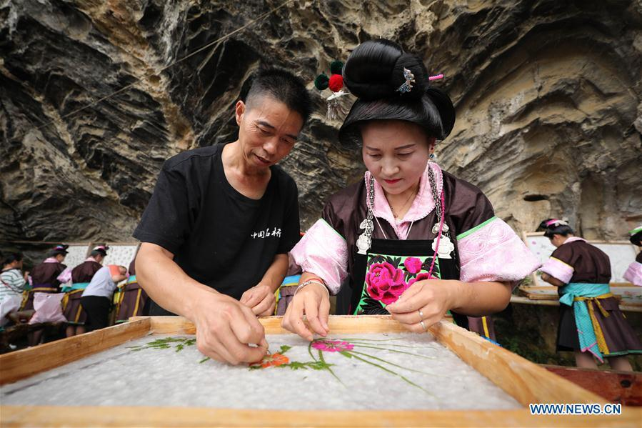 Wang Xingwu (L), a papermaker, teaches a villager to make patterned paper at a workshop in Shiqiao Village of Danzhai County, southwest China\'s Guizhou Province, Sept. 7, 2017. Wang Xingwu, 53, a national intangible cultural heritage inheritor in papermaking, learned the papermaking technique from his family as a child. Besides exerting the old papermaking technique to its full potential, Wang keeps raising product quality and improving the making procedure. With the involvement of plants in the papermaking process, he has created more than 160 kinds of patterned papers and paper crafts. He also develops a kind of handmade white paper more suitable for writing calligraphy and painting. (Xinhua/Huang Xiaohai)
