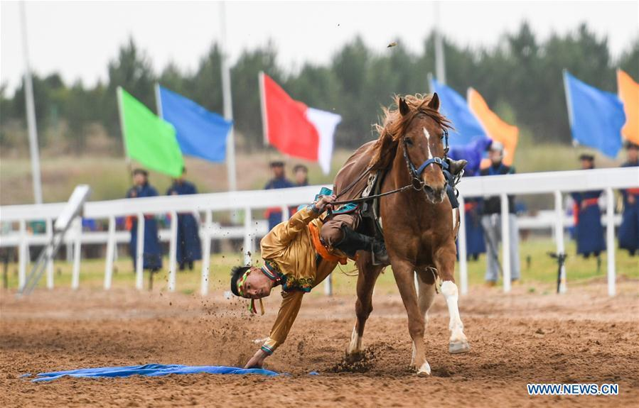 A man picks up a hada when riding a horse during the Genghis Khan Chagan Suluk Nadam Fair in Ejin Horo Banner of Ordos City, north China\'s Inner Mongolia Autonomous Region, April 24, 2019. The two-day fair kicked off on Wednesday, including a variety of traditional activities. (Xinhua/Peng Yuan)