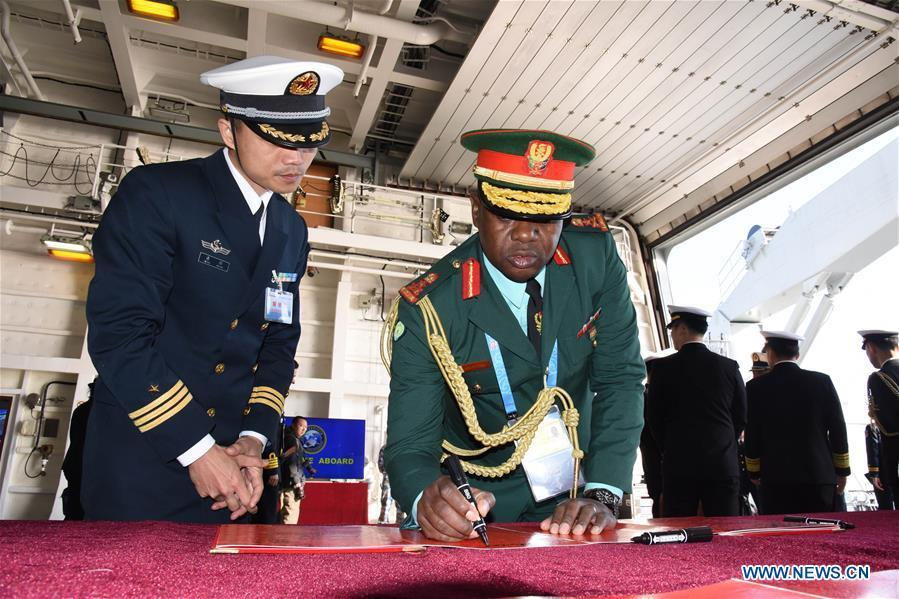 A foreign delegate signs a guest book during his visit to the landing vessel Jinggangshan of the Chinese People\'s Liberation Army (PLA) Navy in Qingdao, east China\'s Shandong Province, April 25, 2019. Foreign delegations invited to participate in the multinational naval events marking the 70th anniversary of the founding of the Chinese PLA Navy visited Chinese vessels and communicated with Chinese soldiers and officers on Thursday. (Xinhua/Li Ziheng)