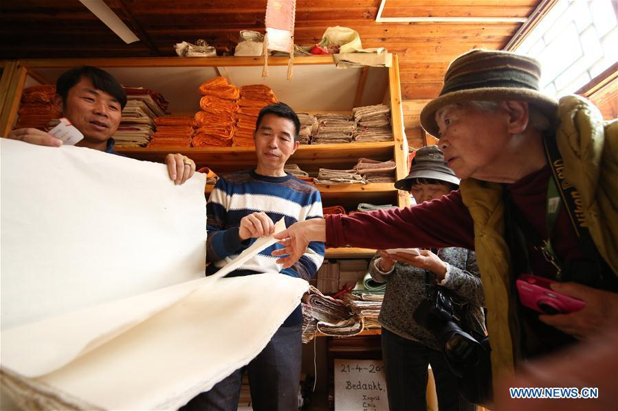 Wang Xingwu (2nd L), a papermaker, introduces his paper product to Japanese tourists at a workshop in Shiqiao Village of Danzhai County, southwest China\'s Guizhou Province, April 24, 2019. Wang Xingwu, 53, a national intangible cultural heritage inheritor in papermaking, learned the papermaking technique from his family as a child. Besides exerting the old papermaking technique to its full potential, Wang keeps raising product quality and improving the making procedure. With the involvement of plants in the papermaking process, he has created more than 160 kinds of patterned papers and paper crafts. He also develops a kind of handmade white paper more suitable for writing calligraphy and painting. (Xinhua/Huang Xiaohai)