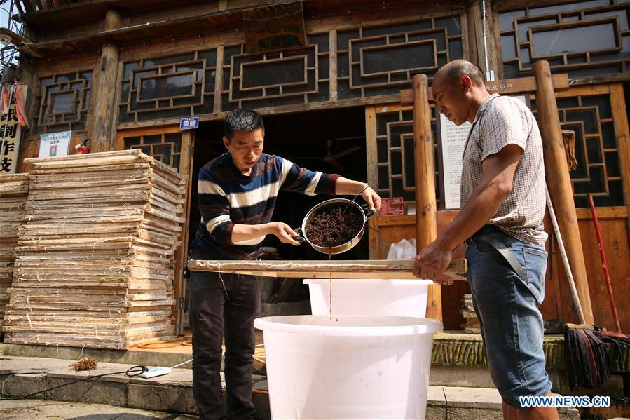 Wang Xingwu (L), a papermaker, filters the plant dyestuff into paper pulp in Shiqiao Village of Danzhai County, southwest China\'s Guizhou Province, April 24, 2019. Wang Xingwu, 53, a national intangible cultural heritage inheritor in papermaking, learned the papermaking technique from his family as a child. Besides exerting the old papermaking technique to its full potential, Wang keeps raising product quality and improving the making procedure. With the involvement of plants in the papermaking process, he has created more than 160 kinds of patterned papers and paper crafts. He also develops a kind of handmade white paper more suitable for writing calligraphy and painting. (Xinhua/Huang Xiaohai)