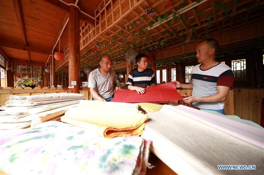 Wang Xingwu (C), a papermaker, talks with other craftsmen about papermaking skills at a workshop in Shiqiao Village of Danzhai County, southwest China\'s Guizhou Province, April 24, 2019. Wang Xingwu, 53, a national intangible cultural heritage inheritor in papermaking, learned the papermaking technique from his family as a child. Besides exerting the old papermaking technique to its full potential, Wang keeps raising product quality and improving the making procedure. With the involvement of plants in the papermaking process, he has created more than 160 kinds of patterned papers and paper crafts. He also develops a kind of handmade white paper more suitable for writing calligraphy and painting. (Xinhua/Huang Xiaohai)