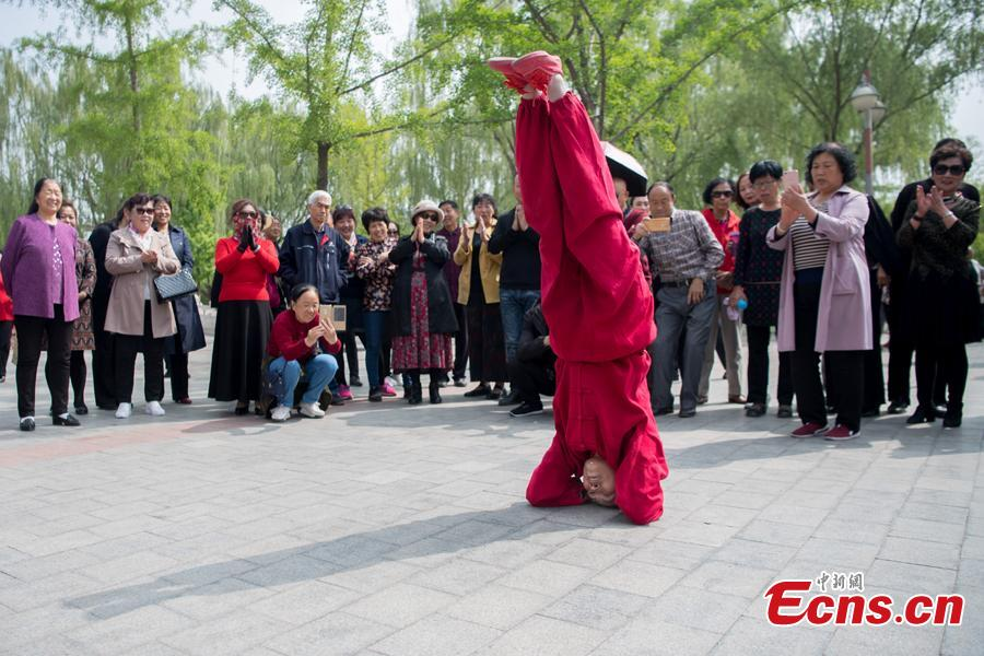 Xiao xuerong, 68, draws a crowd as she practices handstands  in Xuefu Park in Taiyuan, Shanxi Province, April 26, 2019. (Photo/China News Service)