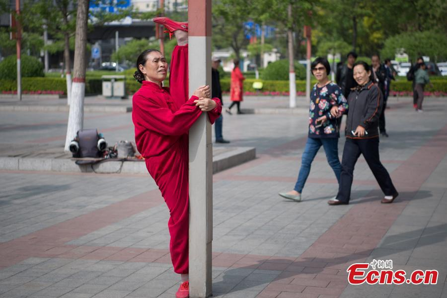 Xiao xuerong, 68, draws a crowd as she practices splits  in Xuefu Park in Taiyuan, Shanxi Province, April 26, 2019. (Photo/China News Service)