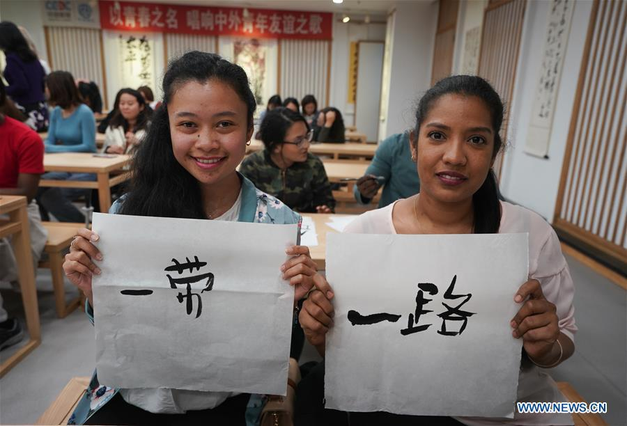 Roxane Estelle Firmin (R) from Mauritus and Nomena Andrianian Razafindrakoto from Madagascar shows the Chinese characters they wrote in Nanjing, capital of east China\'s Jiangsu Province, April 28, 2019. A cultural exchange event between young representatives from Nanjing and foreign students from Nanjing University of the Arts was held in Nanjing. (Xinhua/Ji Chunpeng)