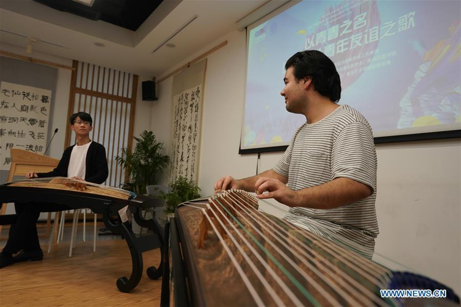 Garzan Yashar (R) from the United States and professional Chinese zither artist Huang Yuzhe play Chinese zither in Nanjing, capital of east China\'s Jiangsu Province, April 28, 2019. A cultural exchange event between young representatives from Nanjing and foreign students from Nanjing University of the Arts was held in Nanjing. (Xinhua/Ji Chunpeng)