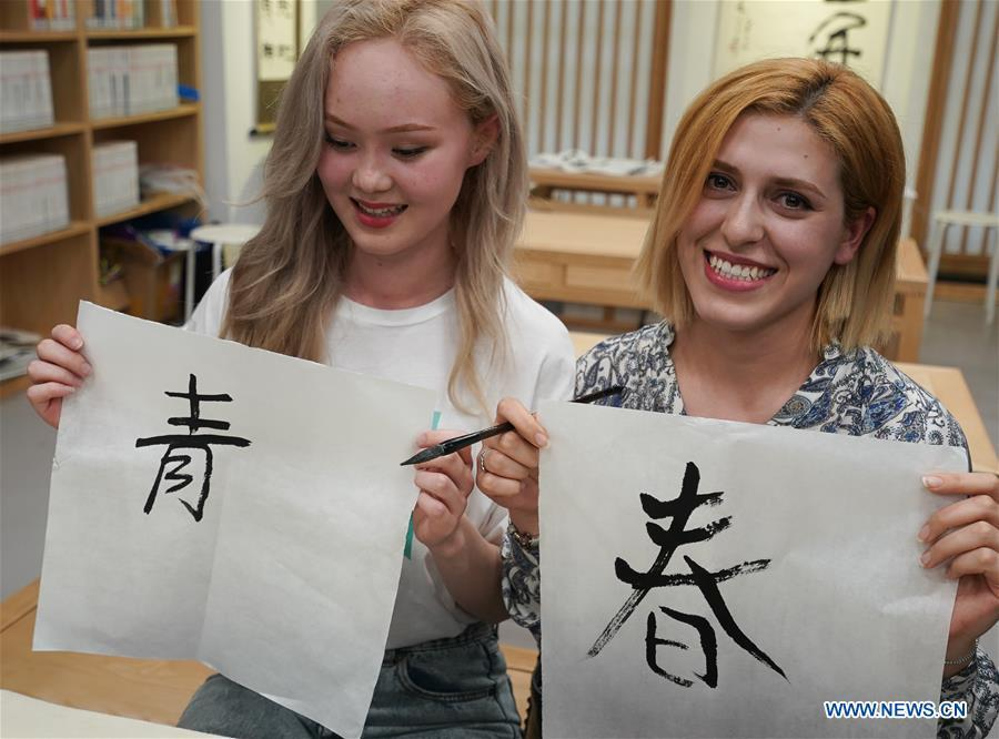 Sara Davlatova (R) from Tajikistan and Aruzhan Kossay from Kazakhstan shows the Chinese characters they wrote in Nanjing, capital of east China\'s Jiangsu Province, April 28, 2019. A cultural exchange event between young representatives from Nanjing and foreign students from Nanjing University of the Arts was held in Nanjing. (Xinhua/Ji Chunpeng)