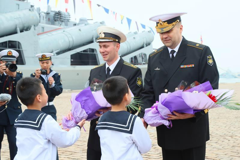 Russian navy officers receive flowers from Chinese children at Qingdao Port during a welcoming ceremony for Russian ships at the Sino-Russia Joint Sea 2019 naval exercise on Monday, April 29, 2019.  (Photo/China Plus)