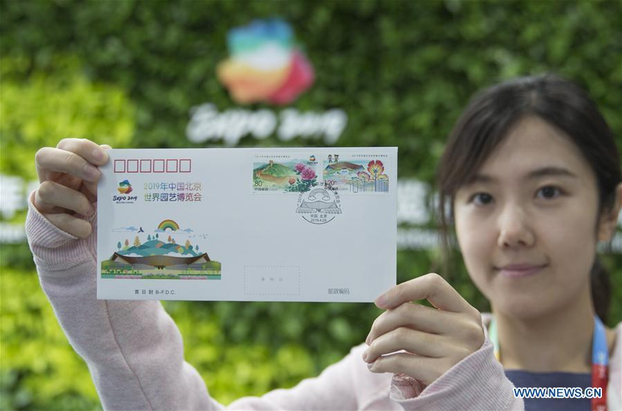 A journalist shows a first-day cover with commemorative stamps issued to mark the International Horticultural Exhibition 2019 Beijing at the media center in Yanqing District of Beijing, capital of China, April 29, 2019. Beijing Stamp Company issued the first-day cover with a set of two commemorative stamps on Monday. (Xinhua/Hou Dongtao)
