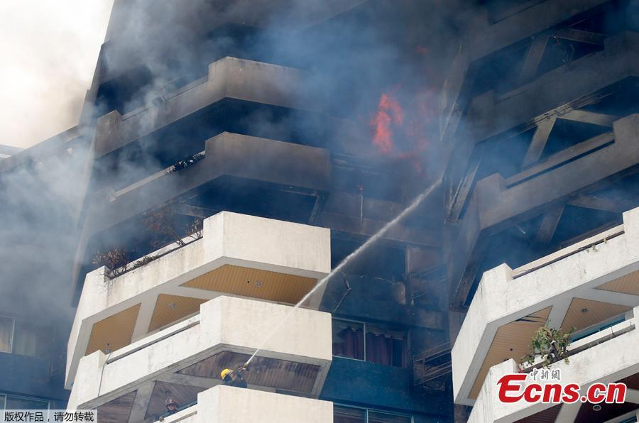 Firemen train their hose on fire in the top floors of a 21-story Pacific Coastal Plaza condominium in Manila, Philippines, April 29, 2019. Officials say more than 100 firetrucks converged Monday to battle the blaze that hit the Pacific Coast Plaza condominium in the Paranaque city area of Manila, where one lane of a coastal road along Manila Bay was closed due to falling debris. A woman died in the accident. (Photo/Agencies)