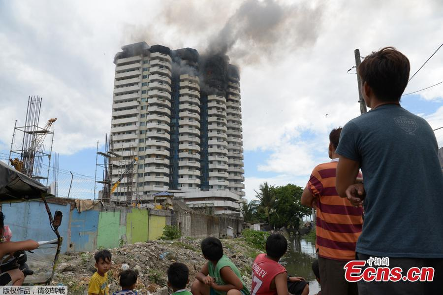 Residents watch as black smoke billows from a 23-storey residential building after a fire broke out in Paranaque City in suburban Manila, Philippines, April 29, 2019. A woman died in the accident. (Photo/Agencies)