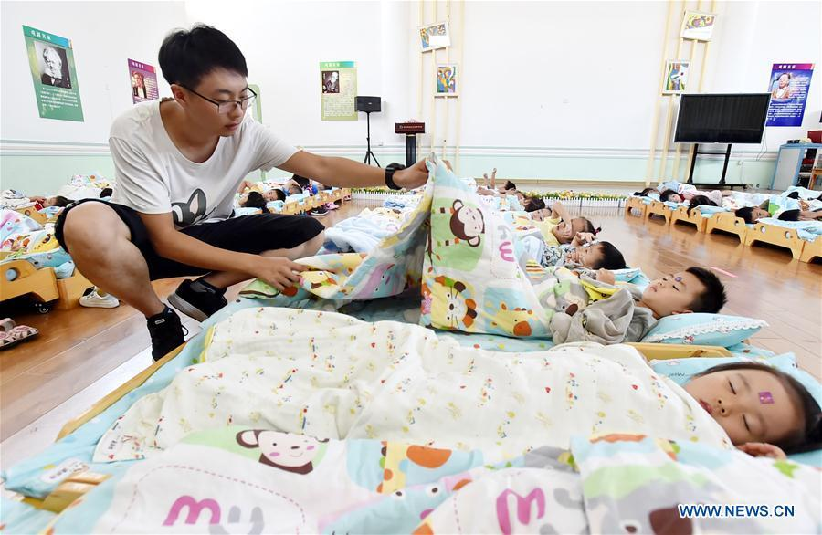 Chen Xuliang, a kindergarten teacher born in the 1990s, covers quilts for children at a kindergarten in Yangzhou, east China\'s Jiangsu Province, Sept. 4, 2018. In Chen\'s view, male teachers are rare, yet can enormously affect children\'s behaviors by different teaching methods and communication styles. Male and female kindergarten teachers are complementary in teaching and thinking. A nation will prosper only when its young people thrive; a country will be full of hope and have a great tomorrow only when its younger generations have ideals, ability, and a strong sense of responsibility. Young people always play a vanguard role in realizing national rejuvenation, which is the mission of the Chinese youth in the new era. In China many young people realize the value of life through hard work. They are writing a brilliant chapter worthy of our times in their efforts to take advantage of their youthful vigor, explore life and contribute to society. (Xinhua/Zhuang Wenbin)
