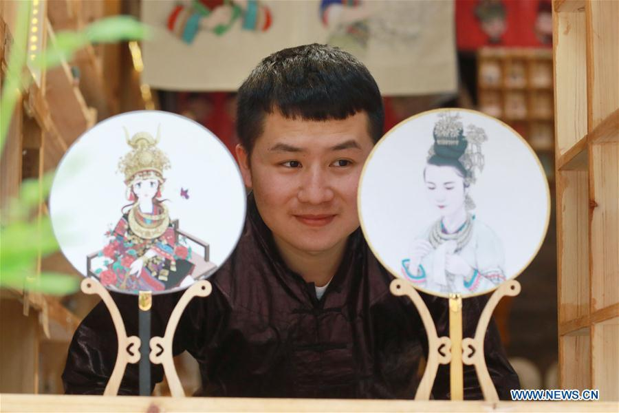 Lan Caisheng, an illustrator born in the 1990s, views fans with his illustrations as coverings at his own studio in Liping County, southwest China\'s Guizhou Province, April 16, 2019. After graduation in 2015, Lan returned to his hometown in Liping County and started a studio to make illustrations and related products featuring ethnic minority cultures including the Miao and Dong ethnic groups. His illustrations are widely known in Liping and recognized by tourists at home and abroad. Lan wishes, through illustrations he made, ethnic minority cultures in Guizhou could reach more people in the future. A nation will prosper only when its young people thrive; a country will be full of hope and have a great tomorrow only when its younger generations have ideals, ability, and a strong sense of responsibility. Young people always play a vanguard role in realizing national rejuvenation, which is the mission of the Chinese youth in the new era. In China many young people realize the value of life through hard work. They are writing a brilliant chapter worthy of our times in their efforts to take advantage of their youthful vigor, explore life and contribute to society. (Xinhua/Ou Dongqu)