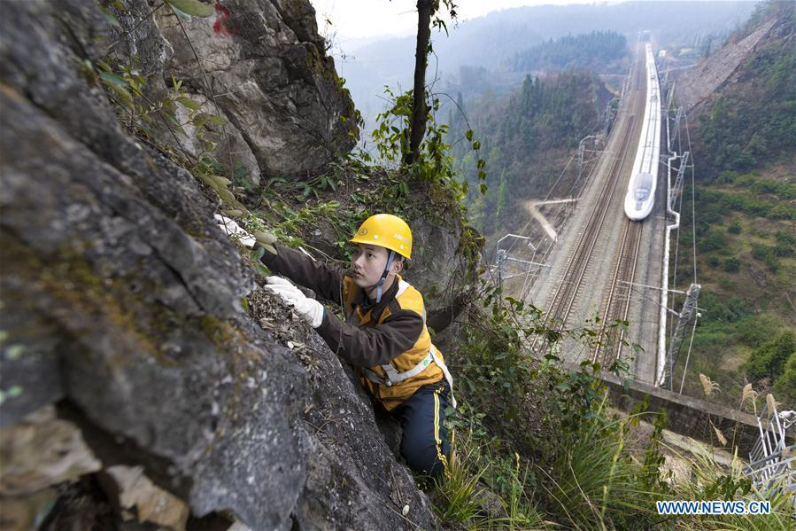 Zhang Yi, a bridge and tunnel worker born in the 1990s, is seen at an observation point while a bullet train runs on the railway in Yichang, central China\'s Hubei province, Jan. 19, 2017. Zhang checks the mountain rock day and night to ensure safety of the Yichang-Wanzhou railway line during the Spring Festival travel rush. A nation will prosper only when its young people thrive; a country will be full of hope and have a great tomorrow only when its younger generations have ideals, ability, and a strong sense of responsibility. Young people always play a vanguard role in realizing national rejuvenation, which is the mission of the Chinese youth in the new era. In China many young people realize the value of life through hard work. They are writing a brilliant chapter worthy of our times in their efforts to take advantage of their youthful vigor, explore life and contribute to society. (Xinhua/Xiong Qi)